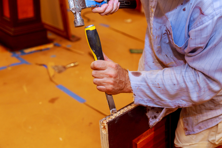 Carpenter makes a hole in new wooden door for the mortise lock with a hammer and chisel.