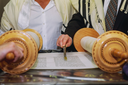 A praying man with a tefillin on his arm and head, holding a Torah scrolls, while reading a pray at a Jewish ritual Bar Mitzvah ceremony .