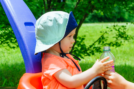 Mother gives daughter drink water bottles with summer green nature park child looking at the a bottle Stock fotó