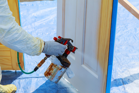 Worker with airbrush painting House repair paint the wooden door in white color with a spray