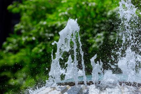 Splash of water in the fountain splashed water drops. Fresh, blue water.