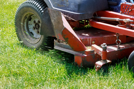 Lawn mower on green grass, mower grass equipment, mowing gardener care work tool, close up view, sunny day