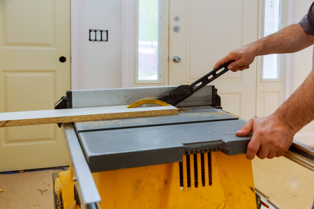 Carpenter cutting wooden trim board on with circular saw. Woodworker works on remodeling home Foto de archivo