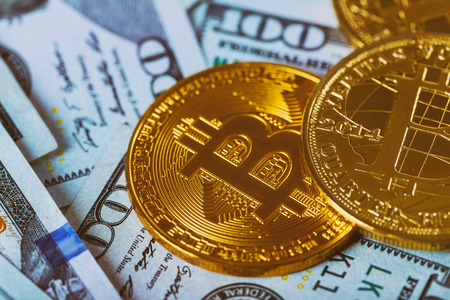 Close-up. Gold Bitcoin on hundred dollars bills. Bitcoin on us dollar bills electronic money exchange concept. Stock Photo