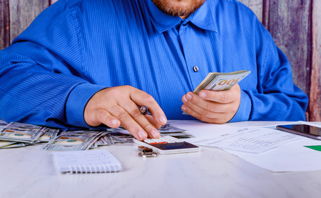 Cropped of bookkeeper using calculator money US dollars banknote money for business investment counting Stock Photo