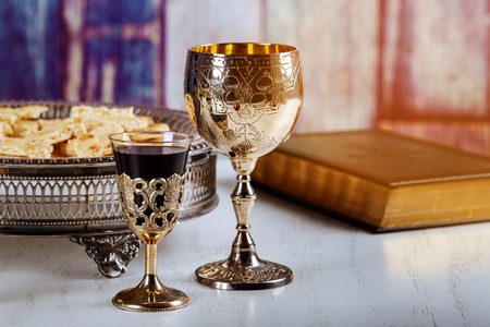 Holy communion on wooden table on church. Cup of glass with red wine, bread on wooden table and Holy Bible