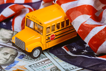 American flag and US banknotes dollar cash money and school bus Standard-Bild - 106594874