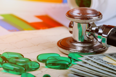 Medical stethoscope head lying on cardiogram chart with pile of pills and dollars closeup. Cardiology care healthy life or insurance concept