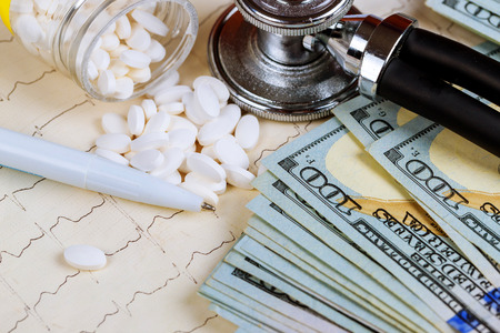 Stethoscope on pills and dollars background with pills and cardiogram