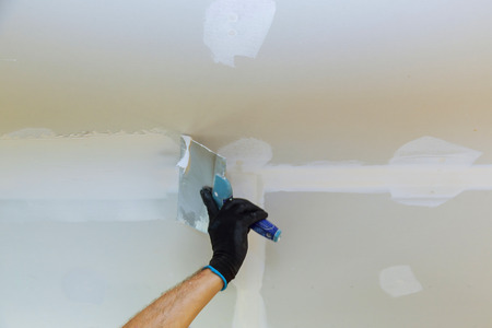 Worker puttied wall using a paint spatula hand worker repairs gypsum plasterboard