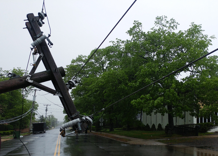 The storm caused severe damage to electric poles power lines over a road after Hurricanepoles falling tilt. Stock Photo - 108686108