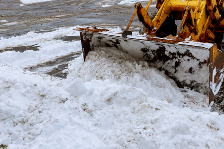 Closeup grader cleaning snow covered road after blizzard excavator for snow removal on a snowy parking lot