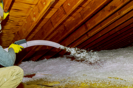Technician spraying blown Fiberglass Insulation between Attic Trusses foam insulation repair tool in the white protect suit applies a construction foam from the gun to the roof. Stockfoto