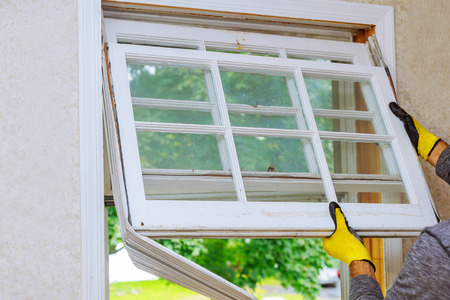 Worker hand removing old window replacing the old wooden window,