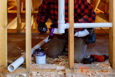 Plumbing building contractor installing plastic PVC pipe in under the bathroom sink Stock Photo