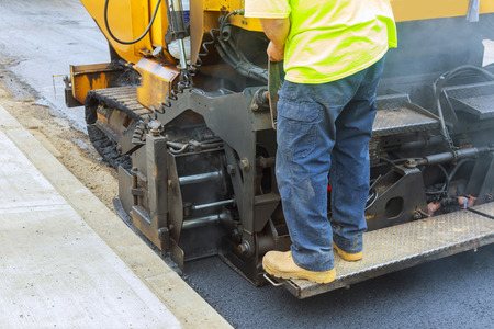 Workers making asphalt with shovels at road construction paving a road