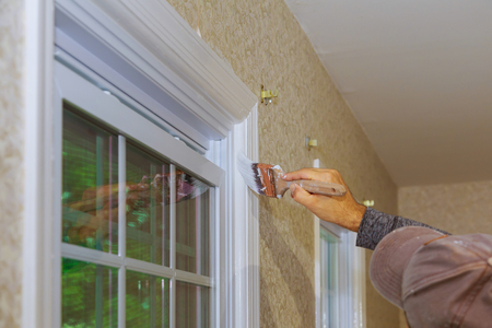 Hand with paintbrush painting a window frame trim white Standard-Bild - 111390540