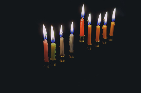 Colorful candles lite on the traditional Silver Hanukkah menorah