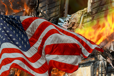 Fire burning and destroyed home in the engulfs small house and the American Flag Imagens