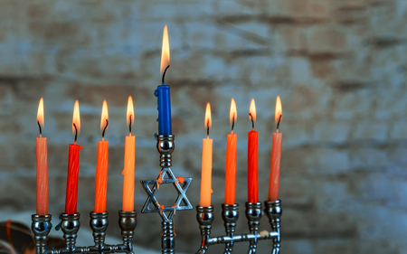 Menorah for the jewish holiday burning hanukkah candles in a menorah on blue background Stock Photo