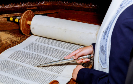 10 NOVEMBER 2018 New York NY Jewish man dressed in ritual clothing Hand of boy reading the Jewish Torah at Bar Mitzvah Bar Mitzvah Torah reading