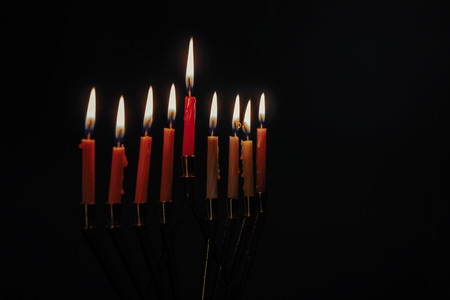Colorful candles lite on the traditional Silver Hanukkah menorah black background
