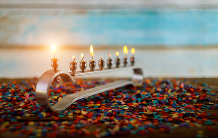 burning hanukkah candles in a menorah on hanukkah celebration with menorah and candles Stock Photo