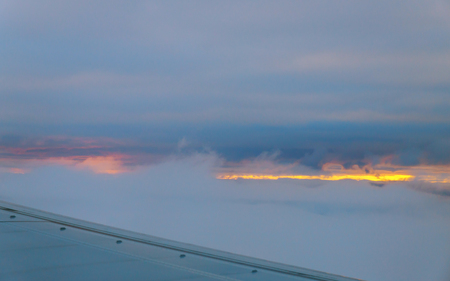Beautiful sunset clouds and sky as seen through window of an aircraft