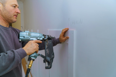 Wall moulding trim air gauge finish nailer man nailed custom house building contractor Banque d'images - 113940309