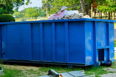 Conteneur à déchets en métal bleu avec débris de construction, poubelle industrielle