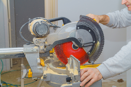 Carpenter cutting wooden trim board on with circular saw. Woodworker works on remodeling home Stock fotó