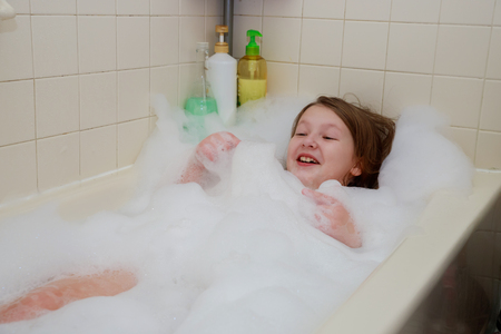 little child is washing her hair in bath playing with foam bubbles