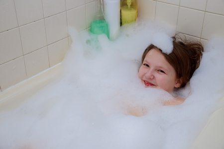 Happy baby in the bath, swimming in the foam. Baby shower.