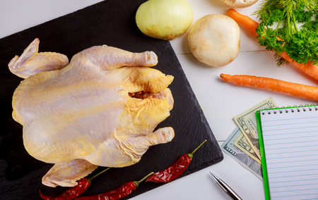 Uncooked chicken on the wooden table with ingredients for marinade. Chicken ready to cook. Marinating meat. Cooking a festive dish chicken for Christmas and Thanksgiving Day.