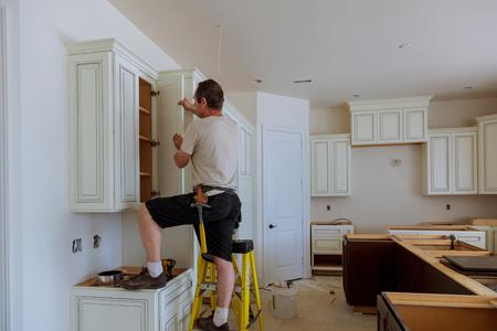 Man installing kitchen cabinets door installation of kitchen 写真素材
