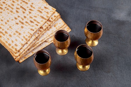 Symbols of Passover background four glasses wine and matzoh jewish holiday bread over wooden board.