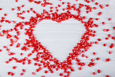 Heart symbol made from fresh organic pomegranate seeds on white background