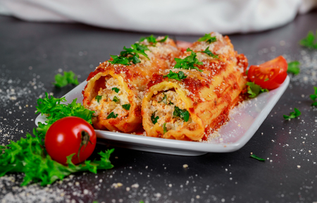 Homemade cannelloni with spinach ricotta meat and tomato sauce Imagens