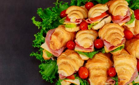 Fresh croissant or sandwich with salad, ham, jamon, tomatoes on wooden background morning breakfast concept
