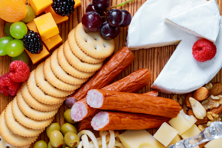 Closeup of various types of gourmet cheese slices with mold green black and green olives and walnuts on wooden platter over blurred background