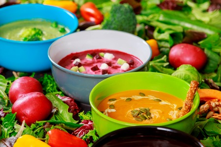 Assortment multi colored soups of vegetable cream soup on a ingredients for soup background