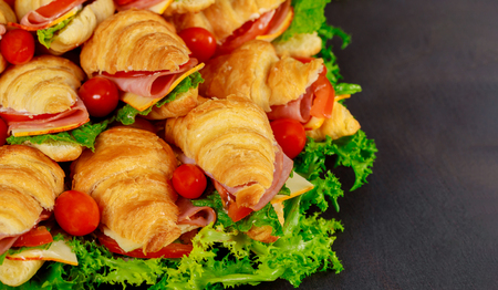 Tasty breakfast. Appetizing croissant with salami and cheese, tomatoes