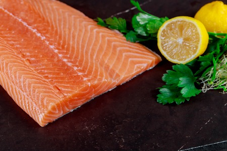 Raw salmon fillet and ingredients for cooking on dark backgroundt top view Stock Photo