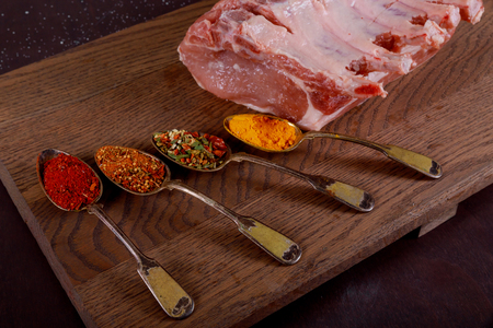 Raw pork steak meat and spices on wooden table