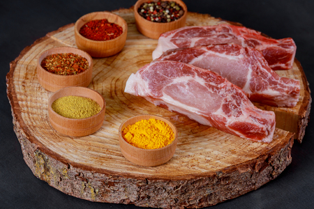 Fresh raw chopped angus on a wooden cutting board with various spices herbs top view Stock Photo