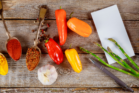 Colorful mix various spices with spoons on herbs garlic and asparagus on old wooden tabletop 写真素材