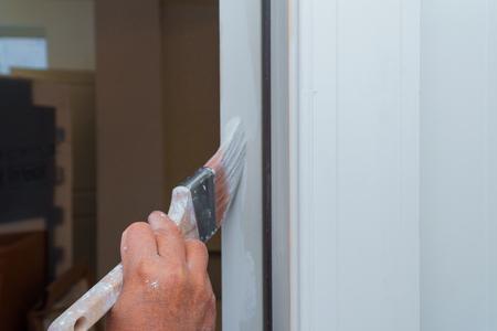 A new house painter painting the door white in door frame Standard-Bild - 116654370