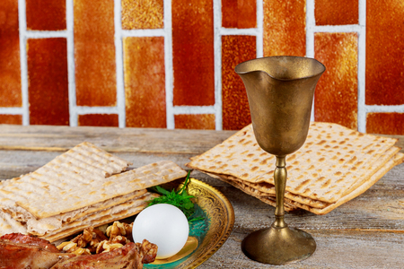 Jewish holiday Passover with wine and seder plate on matzoh passover background wooden table