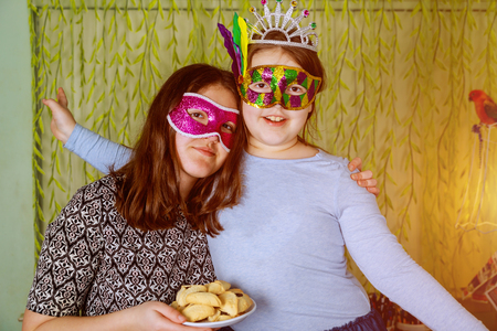 Jewish holiday Purim Happiness of fun and happy expressions In Festive Carnival Masks with hamantaschen cookies or hamans ears