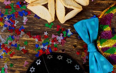 Jewish holiday Purim with carnival mask and homemade hamantaschen cookies, kippah flat lay